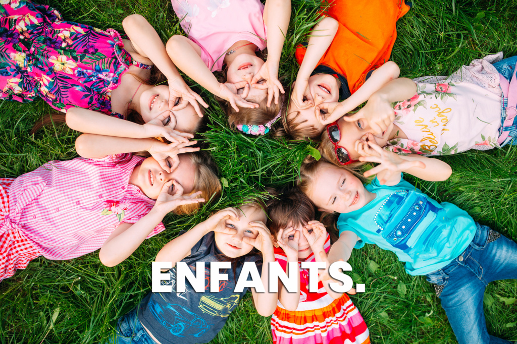 A group of children lying on the green grass in the Park. The interaction of the children